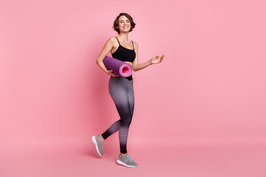 Full body profile side photo of young sportive girl happy positive smile hold mat go walk aerobic isolated over pink color background