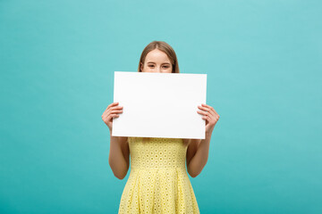 Fototapeta Beautiful woman holding a blank billboard isolated on blue background obraz