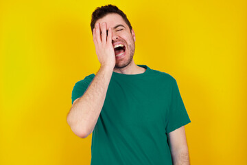 Fototapeta young handsome caucasian man wearing green t-shirt against yellow background makes face palm and smiles broadly, giggles positively hears funny joke poses