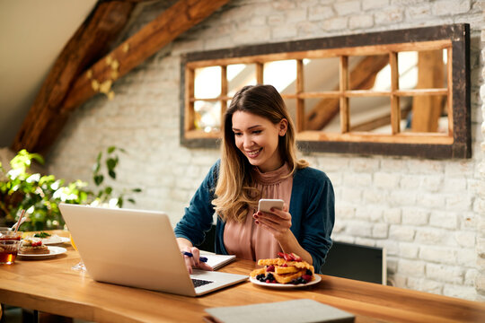 Happy businesswoman using laptop and cell phone while working at home.