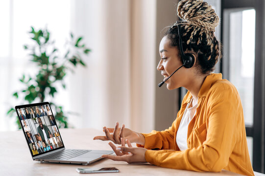 Online business group brainstorm by video conference. Satisfied african american young woman, communicates with business partners by video call uses laptop, multiracial colleagues on a laptop screen