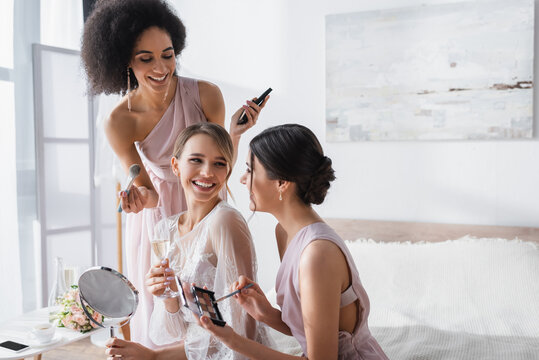 cheerful bride holding mirror and champagne glass near multicultural bridesmaids with decorative cosmetics.