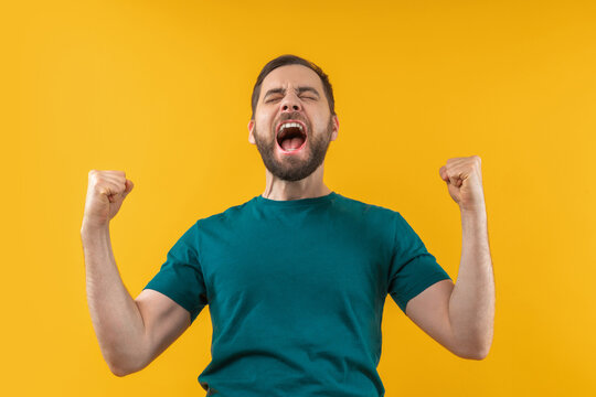 Studio portrait of joyful, excited, glad bearded man with wide open mouth and clenched fists celebrating money win in online lottery or at bookmaker's, isolated over yellow background