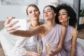 pretty bride with multicultural bridesmaids blowing air kisses while taking selfie on blurred foreground.