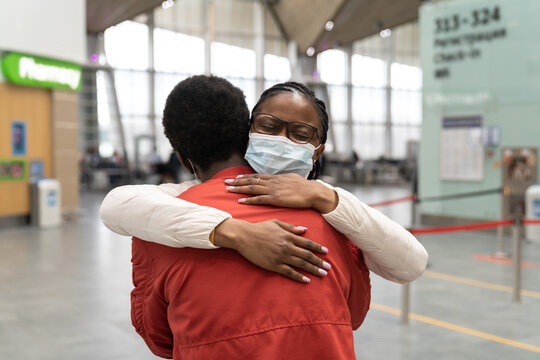 African American couple wear medical face masks hugging, embrace each other within the new normality at airport terminal. Black girl hug lovely boyfriend after long separation due to pandemic Covid-19