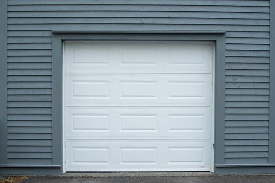 A large white metal panel garage door surrounded with dark gray wood clapboard siding. An asphalt paved entrance to the grey garage door. The boards on the building are narrow horizontal vintage pine.