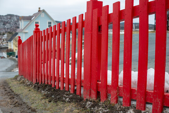 A curved long red wooden picket fence and square posts.  In the background, there's a white country style historic house with black trim under a grey cloudy sky.
