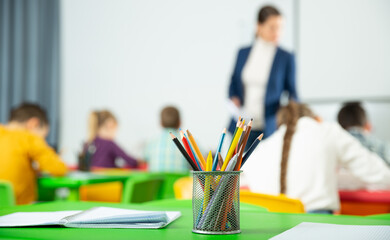 Closeup of multicolored pencils on school table on blurred background with teacher conducting lesson with children