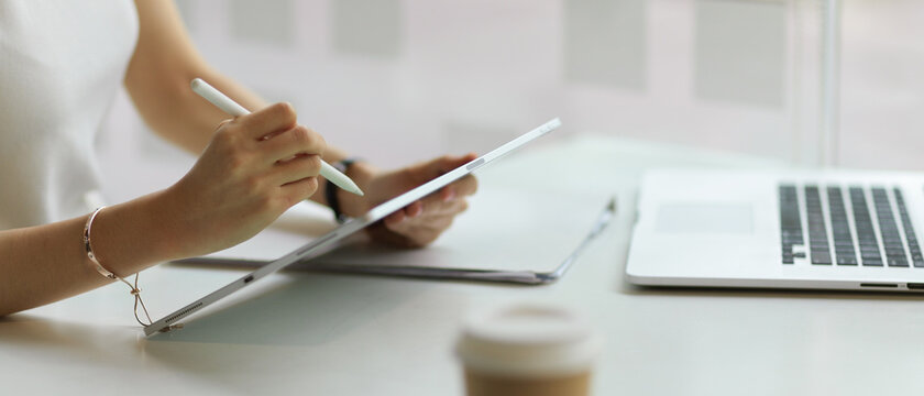 Side view of female hand working with digital tablet on workspace