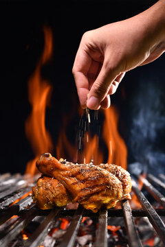 Hand sprinkling salt and spices on grilled chicken leg on the flaming grill