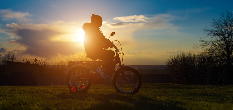 A seven-year-old girl learning to ride a tricycle at sunset in the spring