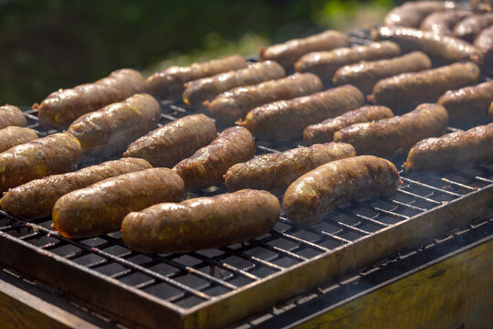 Fried Sausages. Delicious sausages sizzle over the coals on the barbecue grill. Frying sausages on the grill, close-up.