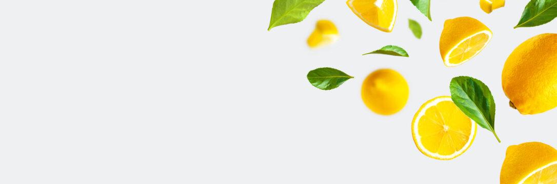 Juicy ripe flying lemons, green leaves on light gray background. Creative food concept. Tropical organic fruit, citrus, vitamin C. Lemon whole and sliced. Summer minimalistic bright fruit background