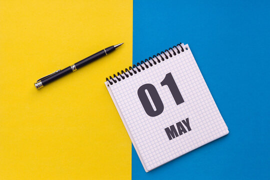 May 1st. Day 1 of month, calendar date. Notebook with a spiral and pen lies on a yellow-blue background