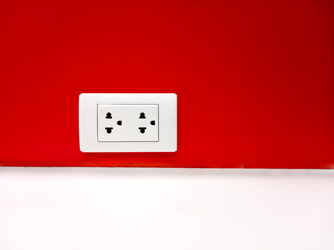 Electrical sockets on  red back walls and white corridors.