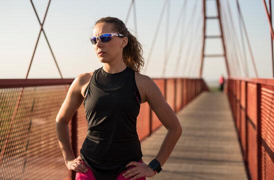 triathlete woman rests posing on pedestrian bridge