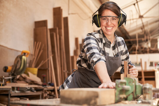Woman as a carpenter trainee at the planer