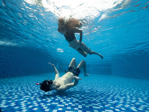 Underwater maternity photoshoot of a young pregnant couple in the swimming pool
