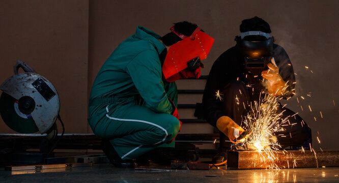 mechanics workers work overtime hardly at night in a factory. Engineers wearing safety outfits with mechanic jumpsuits, gloves, boots, and welding helmets working on metal welding