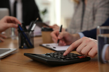Man using calculator at table in office during business meeting, closeup. Management consulting