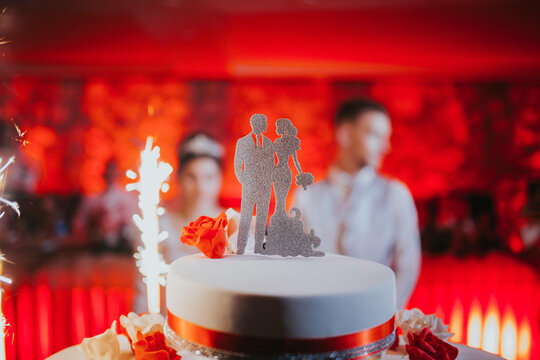Closeup shot of a marriage cake with silhouettes of husband and wife on the backdrop of the couple