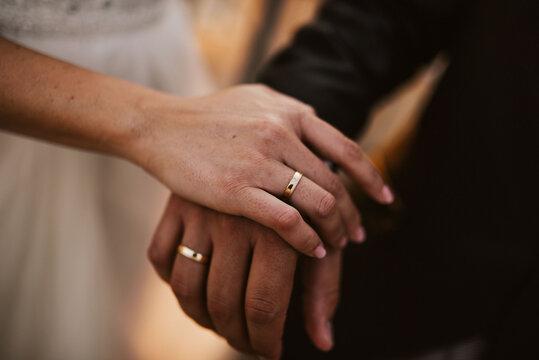 Manos de novios recién casados. Boda. Alianzas. Anillos de matrimonio. Caricia de manos entre esposos. Día de Boda. Amor.