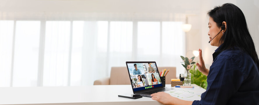 Video conference meeting from home.asian woman say hi to coworker on teleconference collaboration with laptop at home.banner space for display of content