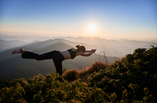 Slim woman doing yoga exercises on incredible nature background. Girl practicing yoga on fresh air in the evening.
