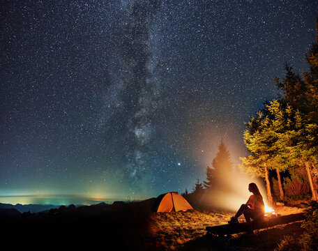 Silhouette of young woman sitting and resting near tent and campfire in the mountains. Concept of relaxation under starry sky with Milky way.