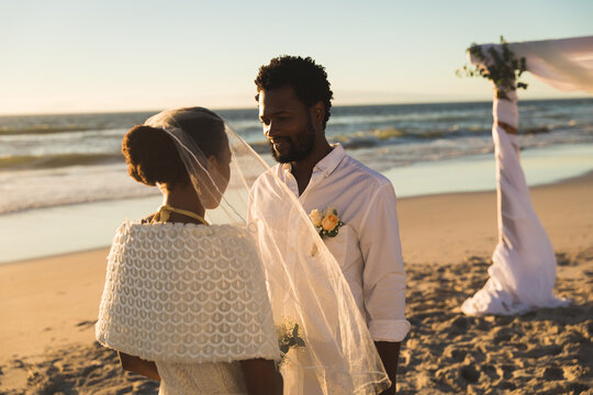 African american couple in love getting married on beach looking to each other