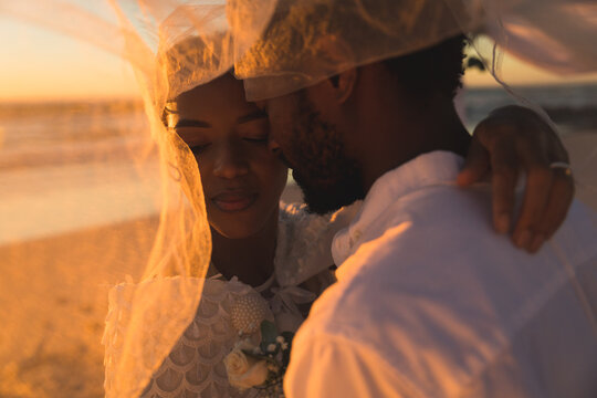 African american couple in love getting married, hugging on beach during sunset