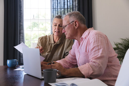 Caucasian senior couple in living room sitting at table using laptop, paying bills and talking