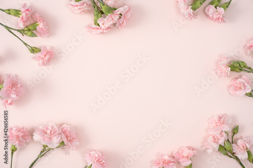 Design concept of Mother's day holiday greeting with carnation bouquet on pink table background