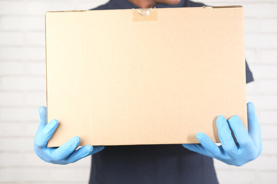 delivery man hand in latex gloves holding card box,