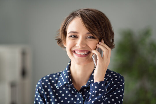 Close-up portrait of attractive cheerful brown-haired girl calling client discussing project at workplace workstation indoors