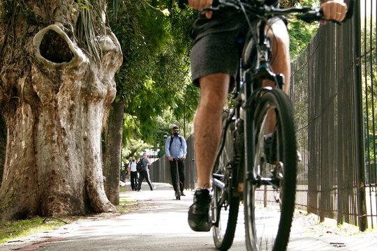 Pessoa andando de bicicleta e scooter elétrico na ciclovia em Curitiba.
