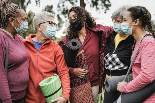 Multiracial women having fun at park outdoor while wearing protective mask for coronavirus outbreak - Multi generational people after yoga class
