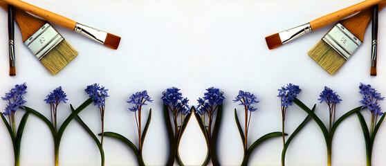 A creative arrangement made of blue flowers and paint brushes on a white background. Paint brushes...