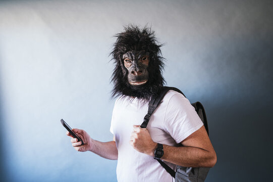 Caucasian man in an angry monkey mask using his smartphone