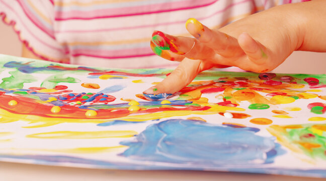 Close up young girl painting with colorful hands and fingers. Art, creativity and painting concept. Horizontal image.
