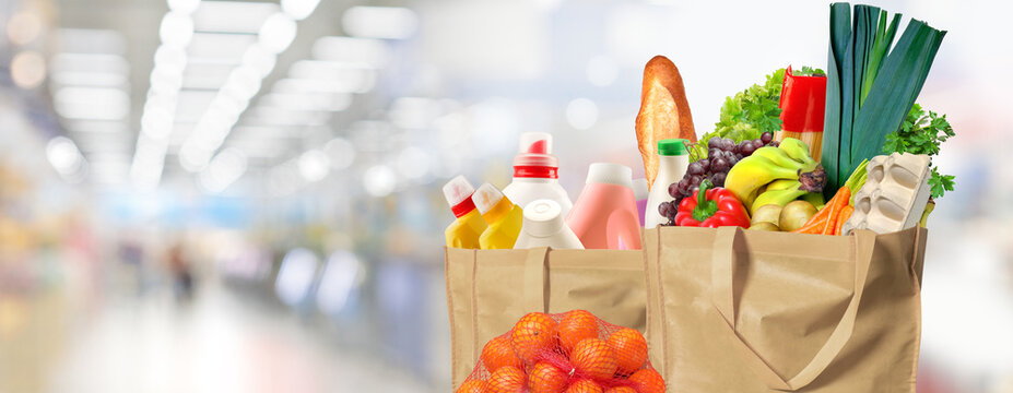 Eco friendly reusable shopping bag filled with bread, fruits and vegetables. Tangerines and ecobag with household chemicals beside a bag.