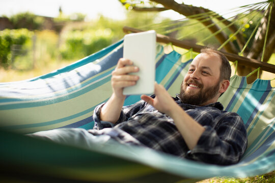 Happy man using digital tablet in sunny summer hammock