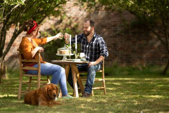 Happy couple with dog toasting glasses at table in summer garden