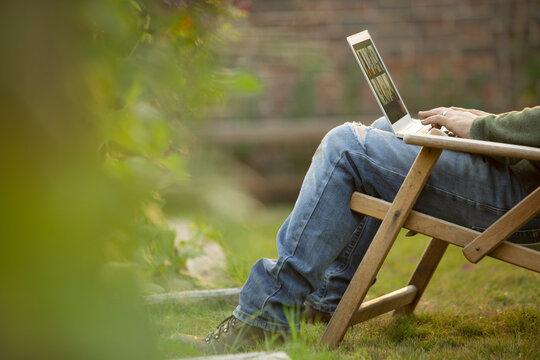 Man using laptop in lawn chair in garden