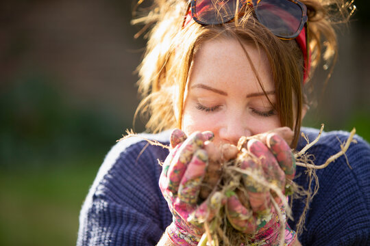 Close up woman smelling fresh harvested potatoes