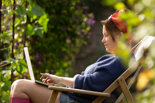 Woman using laptop in sunny summer garden
