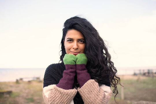 Portrait beautiful woman with long curly black hair on beach