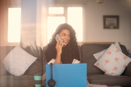Smiling woman working from home talking on smart phone at laptop