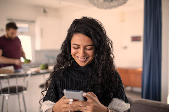 Happy woman using smart phone at home
