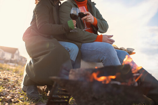 Couple in winter coats drinking red wine by beach fire